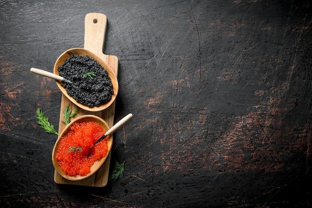 Roter und schwarzer kaviar in den schalen auf dem schneidebrett. auf dunklem rustikalem hintergrund