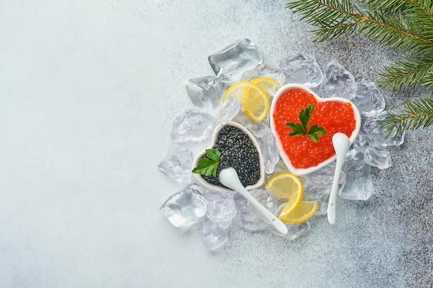 Roter und schwarzer kaviar in der schüssel in form des herzens serviert mit zitrone und eiswürfeln auf grauem hintergrundtisch