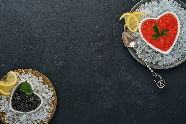 Roter und schwarzer kaviar in der schüssel in form des herzens serviert mit zitrone und eiswürfeln auf schwarzem hintergrundtisch