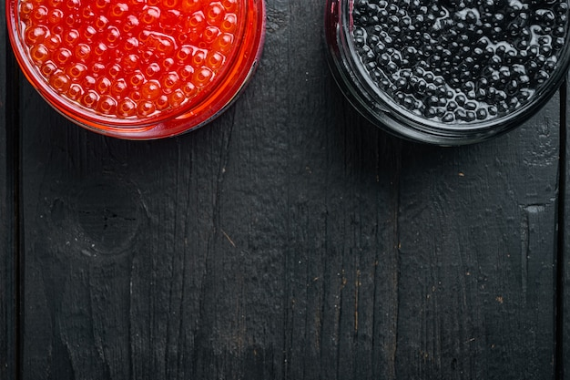 Roter und schwarzer kaviar in glasschüssel, auf schwarzem holztischhintergrund, draufsicht flach mit kopienraum für text