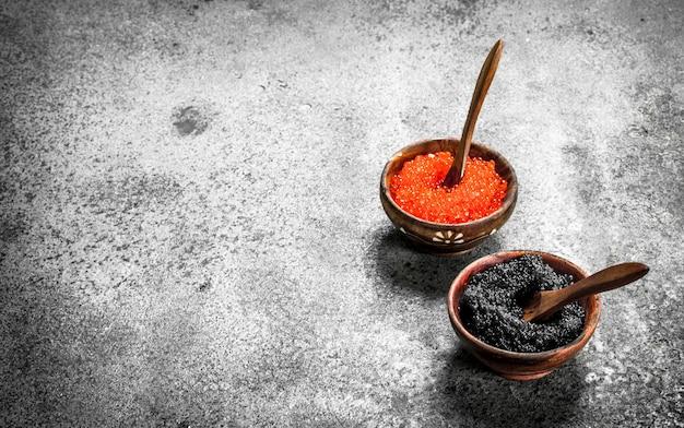 Roter und schwarzer kaviar in holzschalen. auf rustikalem hintergrund.