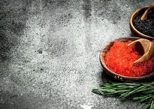 Roter und schwarzer kaviar in schalen mit rosmarinzweigen. auf rustikalem hintergrund.