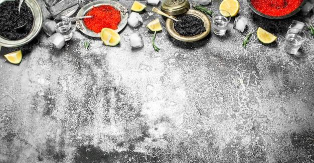 Roter und schwarzer kaviar mit zitrone. auf rustikalem hintergrund.