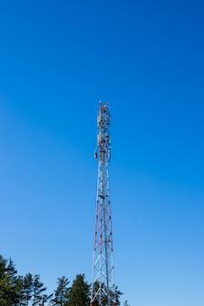 Roter und weißer farbantennenverstärkerturm auf blauem himmel ohne wolke.