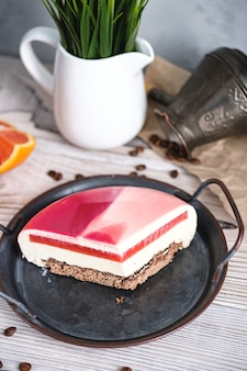 Roter und weißer kuchen mit orangenfüllung. in der nähe auf einem schwarzen tisch sind zutaten orangen, nüsse. rustikaler stil.