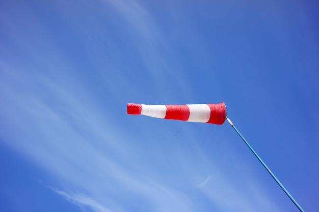 Roter und weißer windsack weht vor blauem himmel.