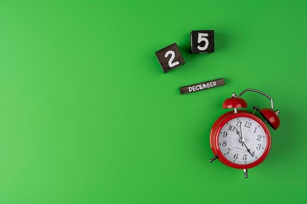 Roter vintage-wecker auf hellgrünem farbhintergrund. ansicht von oben. flach legen mit einem holzkalender, 25. dezember