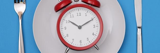 Roter wecker auf weißer platte. diätschema und gesundes lebensstilkonzept