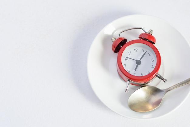 Roter wecker auf weißer platte mit einem silbernen löffel