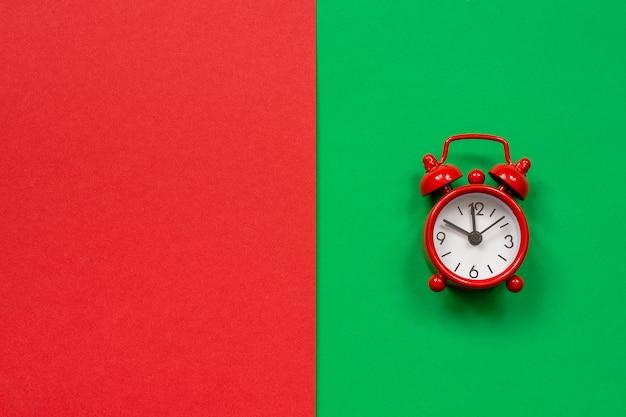 Roter wecker auf zweifarbigem rot-grünem hintergrund