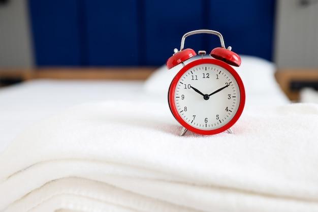 Roter wecker für zehn uhr morgens ist auf handtuch-spa-salon-services-konzept