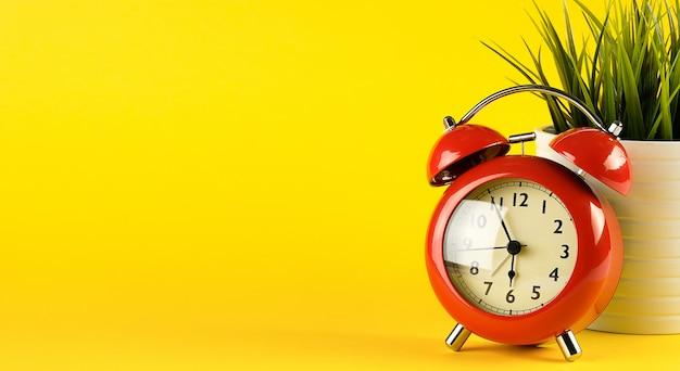 Roter wecker im retro-stil auf einem hellen gelben hintergrund. in der nähe einer blume in einem topf. desktop.