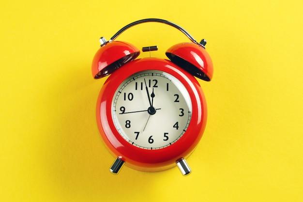 Roter wecker im retro-stil auf einem hellen gelben hintergrund