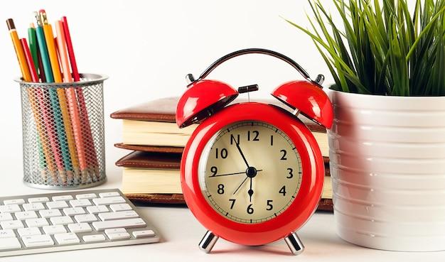 Roter wecker im retro-stil auf einem weißen tisch. daneben steht eine blume in einem topf, buntstifte in einem glas, eine computertastatur und notizbücher. desktop eines freiberuflers oder geschäftsmannes.