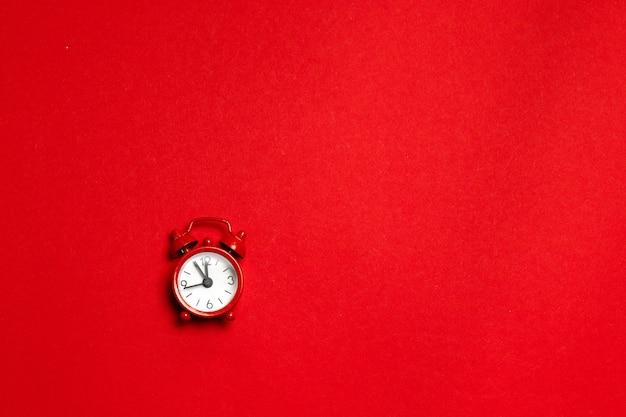 Roter wecker in einer minimalen art auf einem roten hintergrund. flach liegen. ferienkonzept