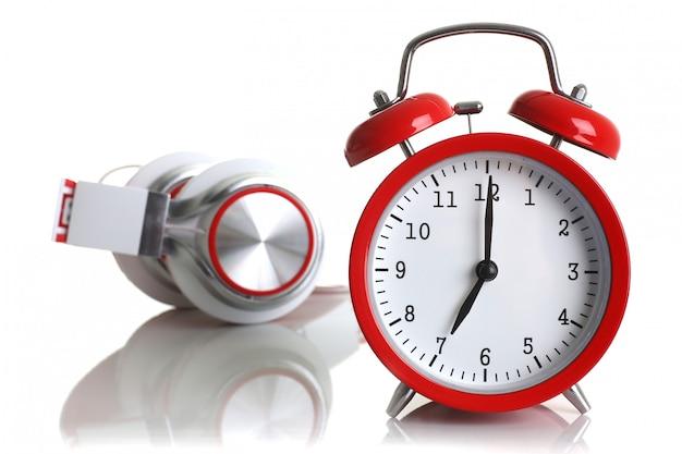 Roter wecker mit den kopfhörern, die auf weißem hintergrund lokalisiert werden, zeigt, dass sieben minuten des morgens es zeit ist, aufzustehen, um aufzuwachen und frühstücksmorgen oder abendstoß zu haben, um zu gehen, musik zu hören.