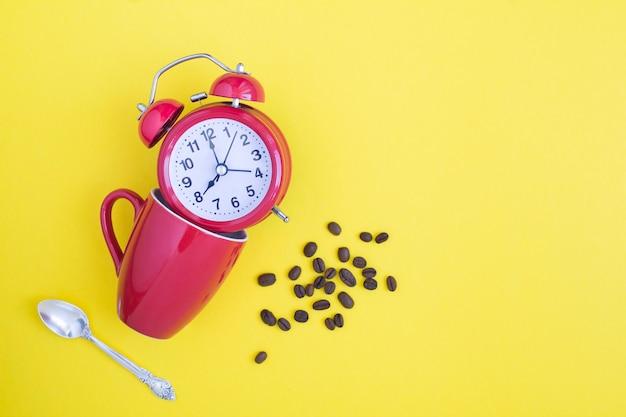Roter wecker, rote tasse und kaffeebohnen auf gelb