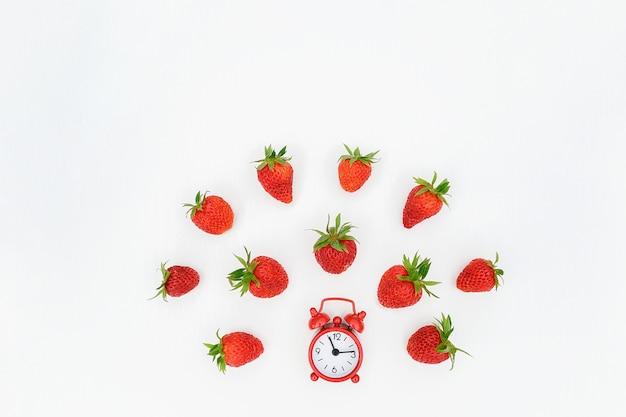 Roter wecker und fliegen, die erdbeerbeere auf weiß zerstreut