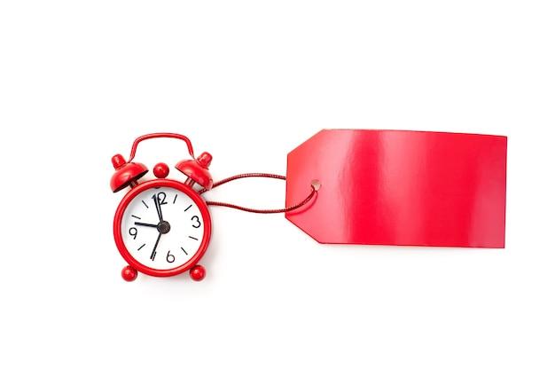 Roter wecker und roter etikettenrohling für eine inschrift auf einem weißen hintergrund