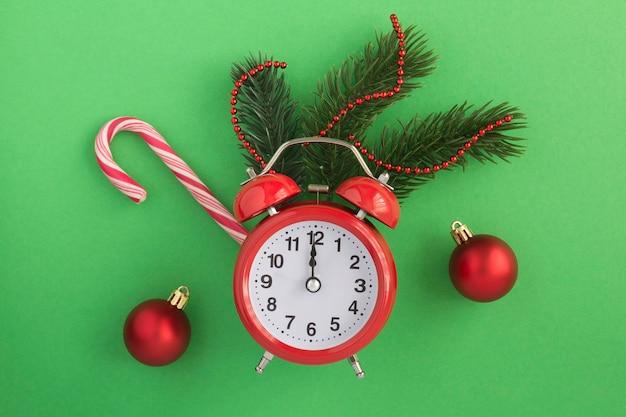 Roter wecker und weihnachtszusammensetzung auf dem grünen hintergrund. draufsicht. speicherplatz kopieren.