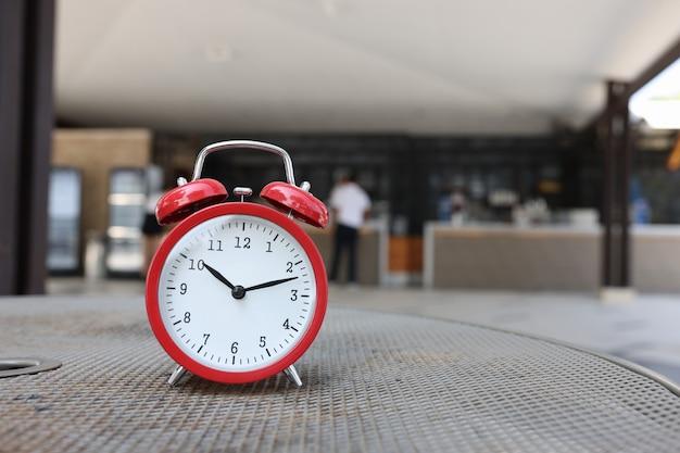 Roter wecker zeigt die zeit von zehn uhr morgens auf dem hintergrund des rezeptionsbeginns des