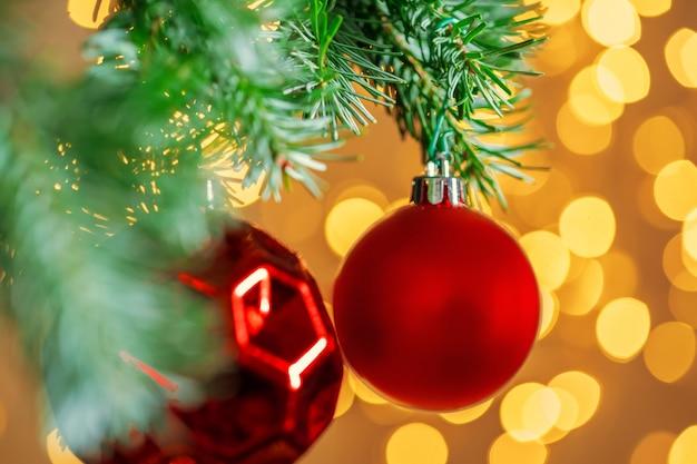 Roter weihnachtsball, der am tannenbaumast über goldenem bokeh hängt, beleuchtet