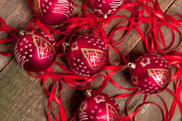 Roter weihnachtsball und -bänder auf holzoberfläche