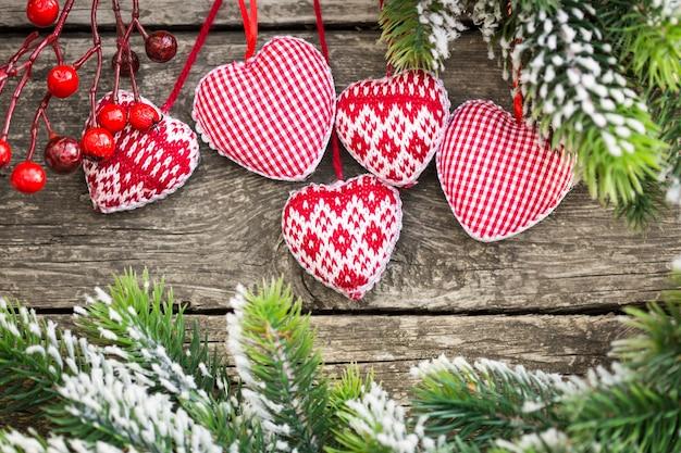 Roter weihnachtsbaumschmuck gerahmter grüner zweig auf holzhintergrund