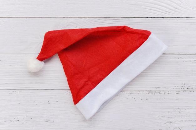 Roter weihnachtshut auf weißem hölzernem tabellenweihnachtsmann-hut für weihnachtsdekoration und -feiertag