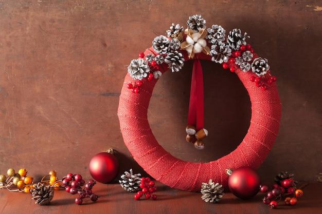 Roter weihnachtskranz auf hölzernem hintergrund