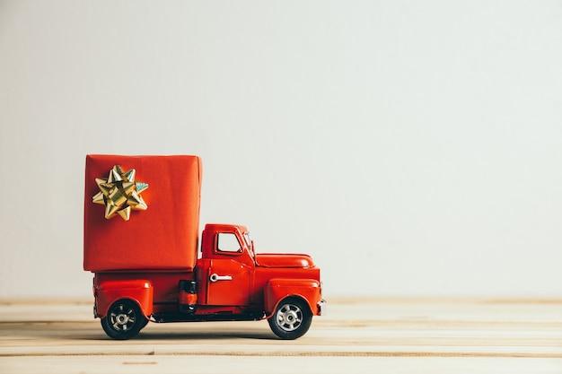 Roter weihnachtslastwagen und geschenk. frohe weihnachten und ein gutes neues jahr konzept.