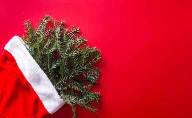 Roter weihnachtsmannhut mit weihnachtsbaumzweigen