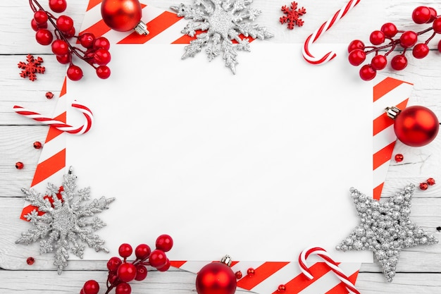 Roter weihnachtsrahmen mit sternen, schneeflocken und süßigkeiten