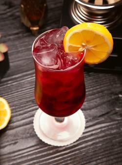 Rotes alkoholcocktail im glas mit eiswürfeln und zitronenscheibe