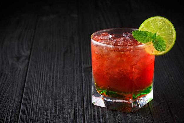 Rotes alkoholcocktail mit minze und kalk auf schwarzem hintergrund