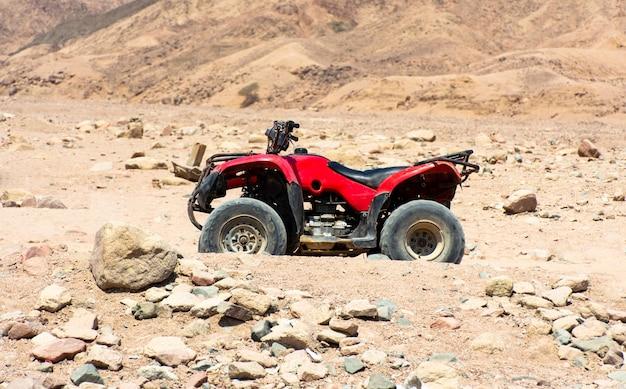 Rotes atv auf dem hintergrund von steinen in der wüste in ägypten