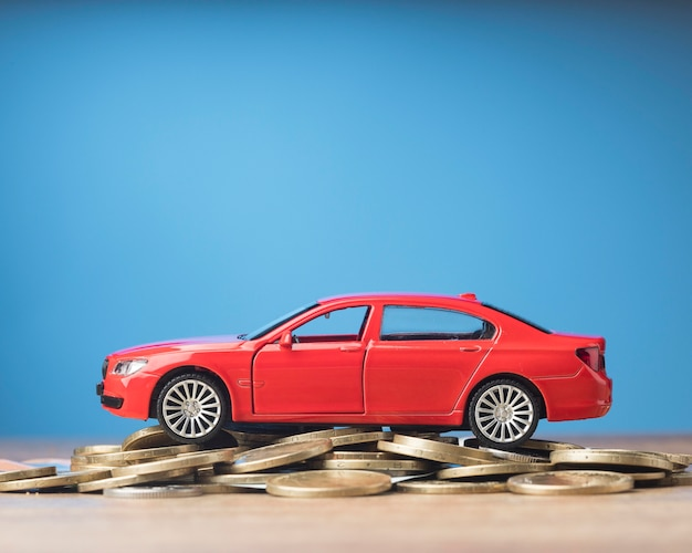 Rotes auto auf einem bündel münzen