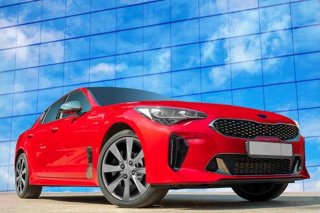 Rotes auto auf einem hintergrund des blauen himmels mit weißen wolken.