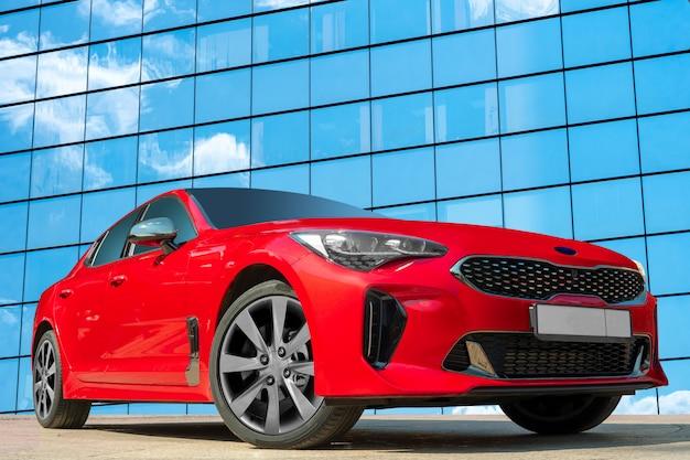 Rotes auto auf einem hintergrund einer widergespiegelten wand eines hauses mit wolkenreflexionen.