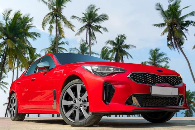 Rotes auto auf einem hintergrund von palmen.