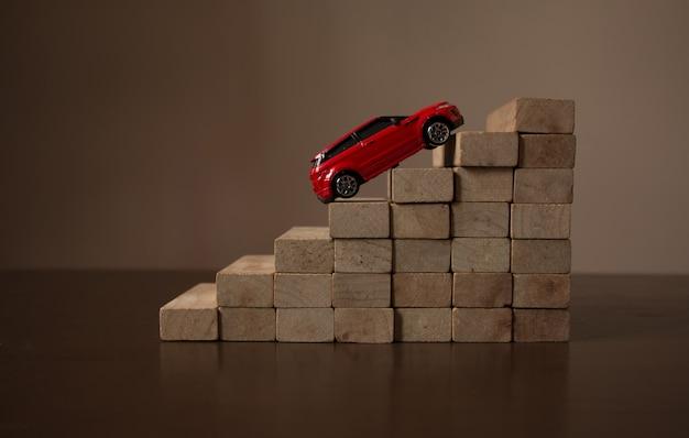 Rotes auto, das auf rollentreppeschritt des hölzernen treppenhausstapels, natürlicher heller heller hintergrund steigt