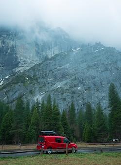 Rotes auto des reisenden parkte in yosemite national park mit schönheitsklippenhintergrund.