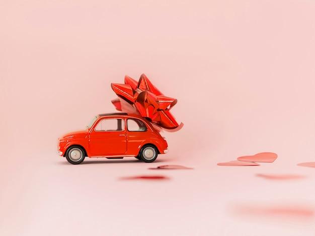 Rotes auto des roten retro- spielzeugs mit rotem bogen für valentinstag auf rosa hintergrund mit herzkonfettis. 14. februar karte. 8. märz, internationaler frauentag. tiefenschärfe