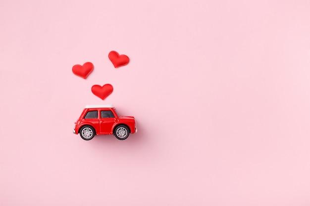 Rotes auto des roten retro- spielzeugs mit rotem bogen für valentinstag auf rosa hintergrund mit herzkonfettis. draufsicht, flach zu legen
