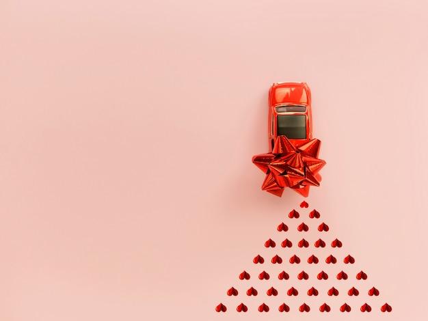 Rotes auto des roten retro- spielzeugs mit rotem bogen für valentinstag auf rosa hintergrund mit herzkonfettis
