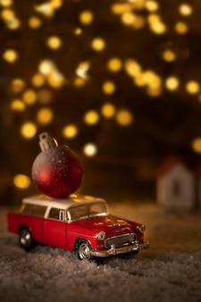 Rotes auto mit einem roten weihnachtsball auf dem dach, schnee, bokeh auf dunklem hintergrund, weihnachtskarte.