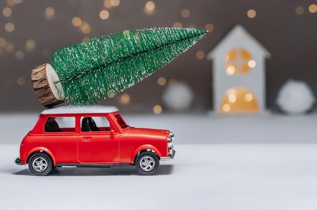 Rotes auto mit einem weihnachtsbaum auf dem dach. vor dem hintergrund des hauses. konzept zum thema weihnachten und neujahr.