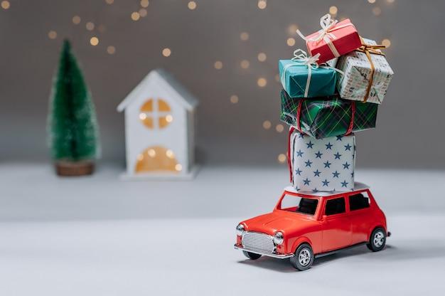 Rotes auto mit geschenken auf dem dach. vor dem hintergrund des hauses und des baumes. konzept zum thema weihnachten und neujahr.