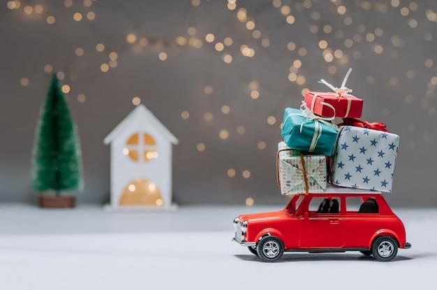 Rotes auto mit geschenken auf dem dach. vor dem hintergrund eines hauses und eines weihnachtsbaumes. konzept zum thema weihnachten und neujahr.