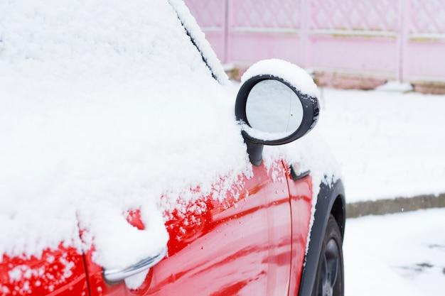 Rotes auto nach schneefall bedeckt. blick auf eine seitenspiegelmaschine